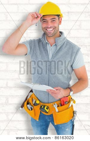 Portrait of smiling manual worker holding clipboard against white wall