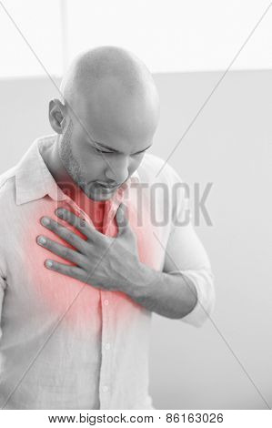 Casual young man with chest pain standing against white background