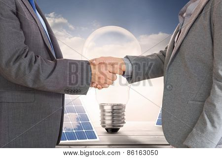Close up on two businesspeople shaking hands against light bulb and solar panels on floorboards in the sky