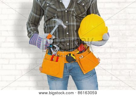 Manual worker wearing tool belt while holding hammer and helmet against white wall