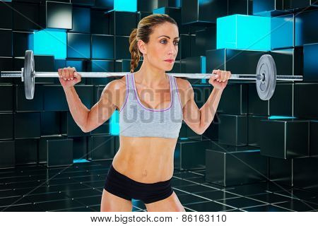 Strong female crossfitter lifting barbell behind head against blue and black tile design