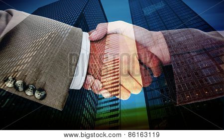 Side view of business peoples hands shaking against low angle view of skyscrapers