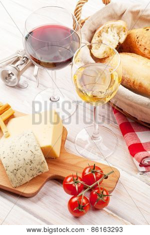 White and red wine, cheese and bread on white wooden table