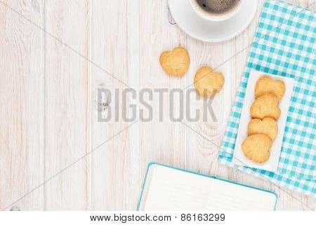 Coffee, heart shaped cookies and notepad on white wooden table with copy space
