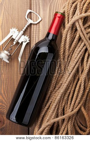 Red wine bottle and corkscrew over rustic wooden table background