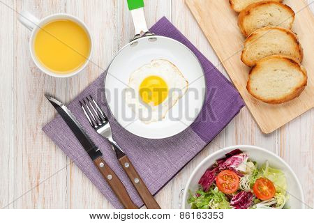 Healthy breakfast with fried egg, toasts and salad on white wooden table. Top view