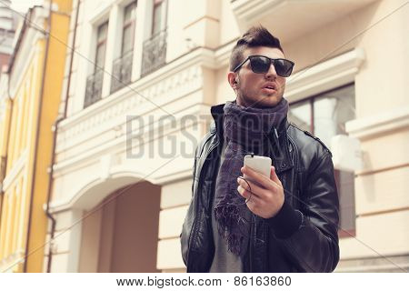 Guy In Sunglasses And Earphones On The Street