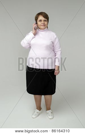Full-length portrait of adult woman speaking on phone
