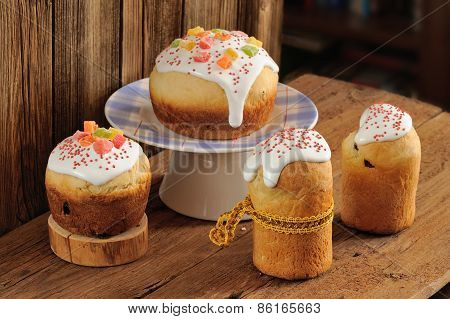 Kulich, Russian Easter Sweet Breads Decorated With Icing And Candied Fruits On Wooden Background