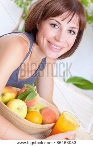 Portrait of beautiful woman eating fresh ripe fruits and drinking juice at home, loss weight, dieting and healthy nutrition concept