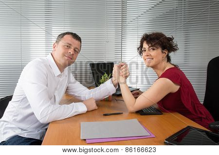 A Man And Woman With Hands Clasped Arm Wrestling