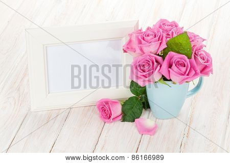 Blank photo frame and pink roses. Over wooden table