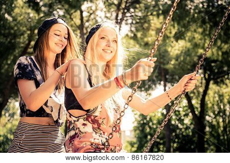Women Playing On A Swing At Sunset