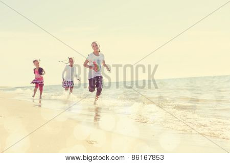 Blurred children running on the beach, focus on sand in foreground. Instagram effect