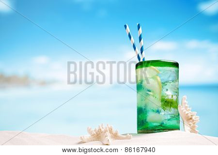 mojito cocktail with ice, rum, lemon and mint in a glass on beach sand and seascape