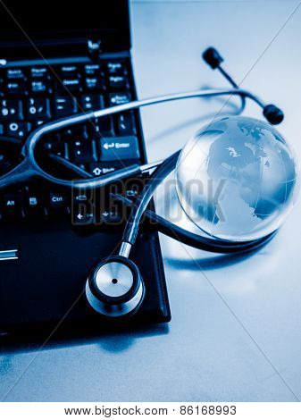 Glass globe and stethoscope on a computer keyboard.blue toned images.