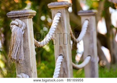 Wooden Footbridge Ropes In Daylight With Blurred Forest Background