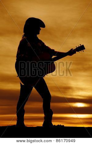 Silhouette Of A Woman Standing In The Sunset Playing A Guitar