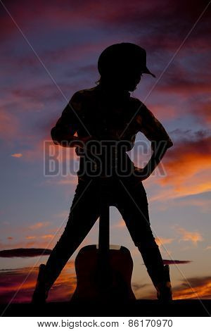 Silhouette Of Cowgirl Standing With A Guitar Between Her Legs