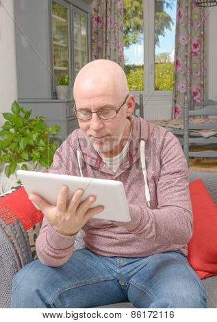 A Man With Glasses Looking At A Tablet