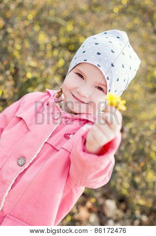Happy Little Girl Holding A Yellow Flower