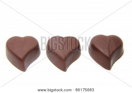 three chocolate candy in the shape of heart on white background