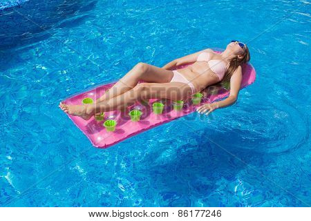 beautiful girl floating on a mattress in the sea or swimming pool