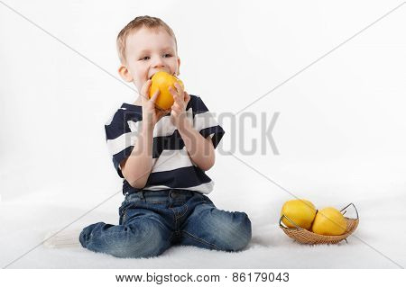 Little Cute Boy Eating A Yellow Apple On White Background