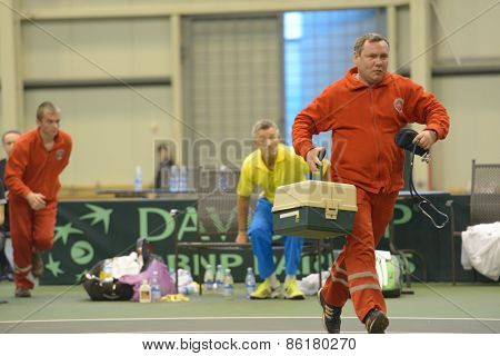 DNEPROPETROVSK, UKRAINE - APRIL 5, 2013: The medical team rushes to the rescue spectator during the Davis Cup match Ukraine vs Sweden. The child fell from the stands during the match