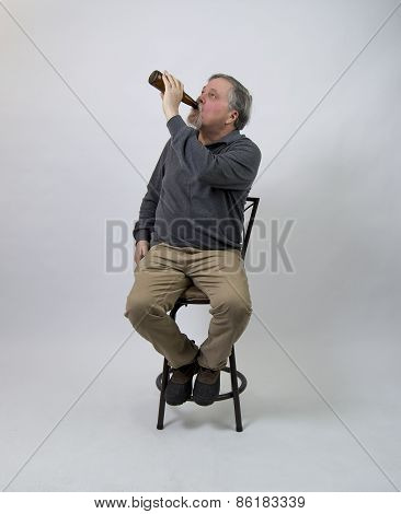 Older Man Sitting On Stool Drinking Beer From Bottle
