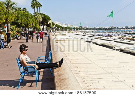 Tourists And The Weather Along The Boulevard De La Croisette In Cannes, France.