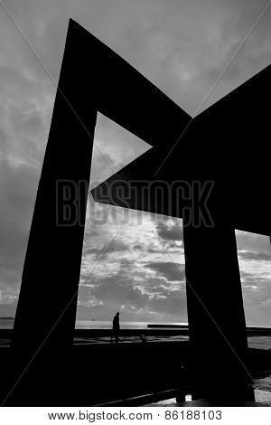 Man is walking under silhouette of Human Rights Monument near seaside with cloudy background
