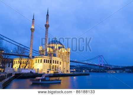 Colorful Ortakoy mosque and Bosphorus Bridge reflection on the sea at the evening