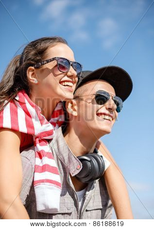 summer holidays, relationships and teenage concept - smiling teenagers in sunglasses having fun outside