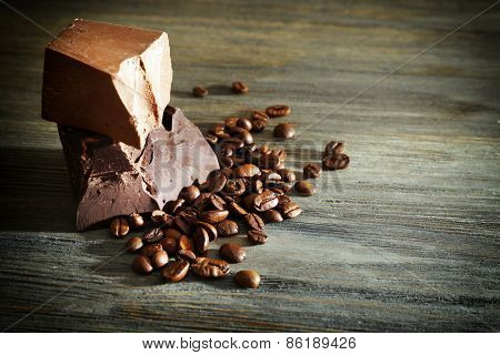 Chocolate bars with coffee beans on wooden background
