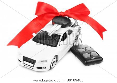 Keys with red bow on car as present isolated on white
