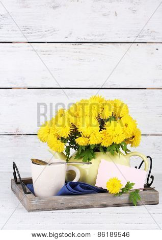 Yellow flowers in decorative teapot on wooden background