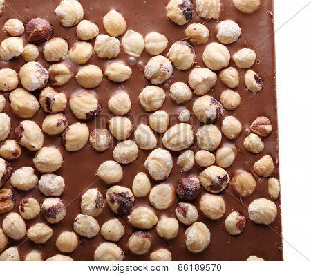 Milk chocolate bar with hazelnuts close up