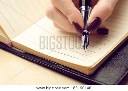 Female hand writing in diary by pen on wooden table background