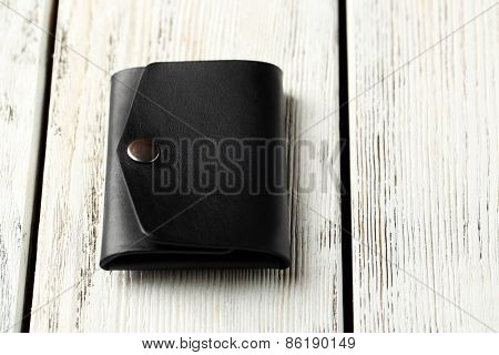 Hand made leather man wallet on white wooden background