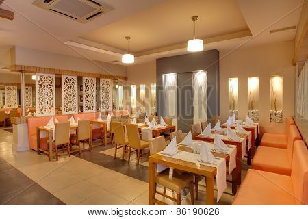 Interior of a luxury restaurant in a hotel, during evening.