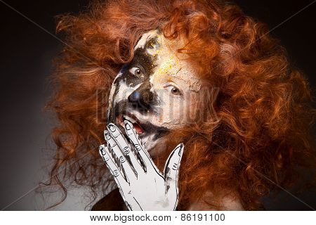 Red haired woman with face art and creative make up. Curly hair style. Black and white face art. Fan
