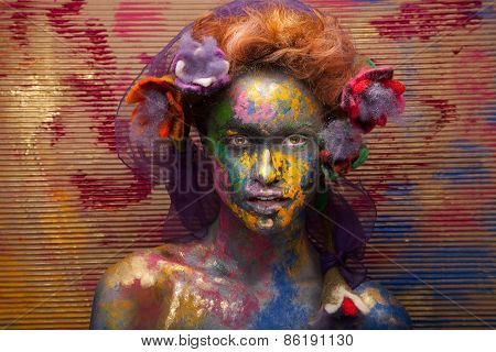 Woman in paint. Attractive and sexy girl. Face art. Bright make up and body art. Flowers in hair. Ov