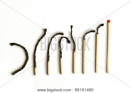 Row of burnt matches and whole one on light background