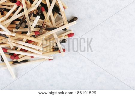 Pile of burnt and whole matches on light background