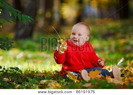 Cheerful baby in a red dress playing with yellow leaves