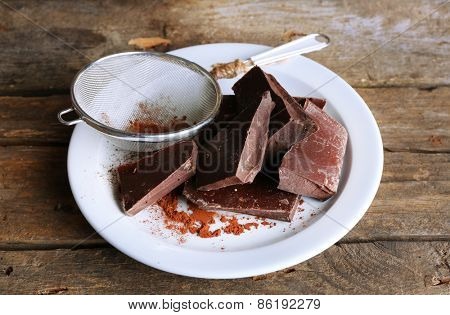 Bittersweet chocolate chunks with strainer of cocoa on white plate and rustic wooden planks background