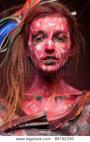 Young woman with creative face-art over dark red background. sensual girl with colorful bodyart.