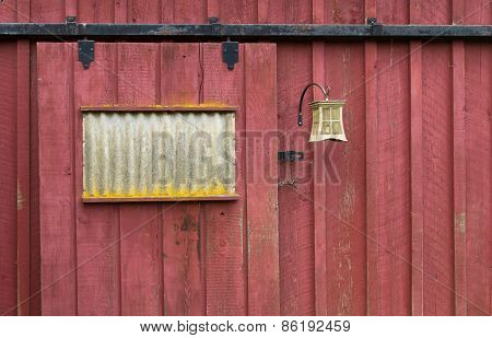 Weathered Red Barn Door With Light Fixture