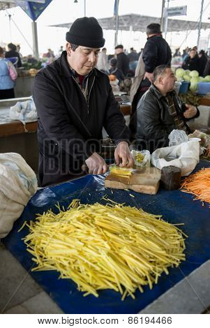 SAMARQUAND, UZBEKISTAN - MARCH 14, 2015: City grocery market. Man sells yellow carrots for Uzbek national dish - plov.